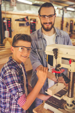 Handsome carpenter and his son in protective glasses are looking at camera and smiling while working with wood and drilling machine in the workshop