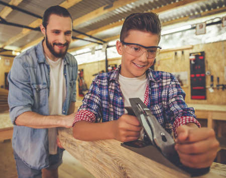 Handsome teenage carpenter in protective glasses and his father are smiling while working with wood and carpenter's plane in the workshop Фото со стока - 62237003
