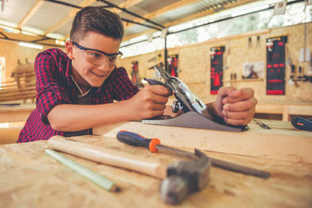 Handsome teenage carpenter in protective glasses is smiling while working with wood and carpenters plane in the workshop