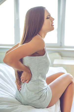 Beautiful young woman in gray singlet is keeping hands on her back, feeling pain, sitting on bed at home