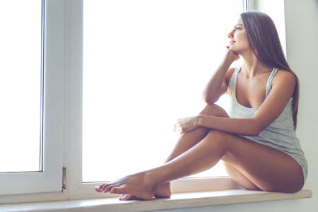 singlet: Beautiful sexy young woman in gray singlet is looking out the window, dreaming and smiling while sitting on the window sill at home Stock Photo