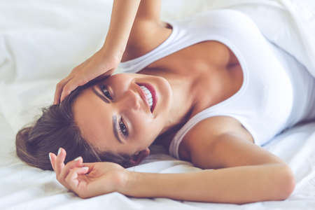 undershirt: Portrait of beautiful sexy young woman in white undershirt looking at camera and smiling while lying in the bed Stock Photo