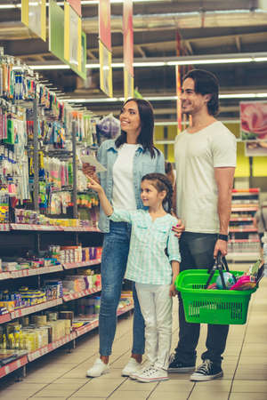 Beautiful young parents and their cute little daughter are smiling while choosing school stationery in the supermarket. Girl is pointing