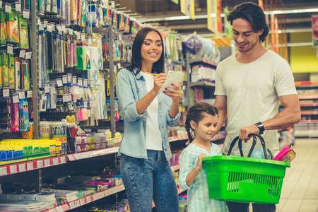 美しい若い両親とかわいい小さな娘はスーパーで文房具を選択しながら笑っています。ママは一覧でノートを作っています。