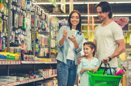 Mooie jonge ouders en hun schattige kleine dochter lachen tijdens het kiezen van schoolartikelen in de supermarkt. Mama maakt notities in de lijst