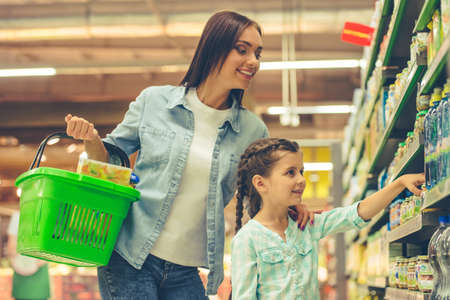 mum and child: Beautiful young mother and her cute little daughter are smiling while choosing food in the supermarket