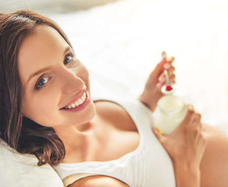 Portrait of beautiful pregnant young woman eating yogurt, looking at camera and smiling while lying in bed at home