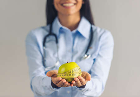 Cropped image of beautiful young dietitian holding an apple and a tape measure and smiling, on gray background Stock Photo