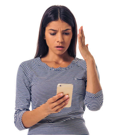 embarrassment: Beautiful young girl in casual clothes is using a smartphone, gesturing and showing embarrassment, isolated on white Stock Photo