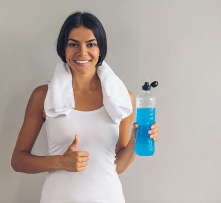 Beautiful young sportswoman in white singlet is holding a bottle of water, showing Ok sign, looking at camera and smiling, on gray background Stock Photo