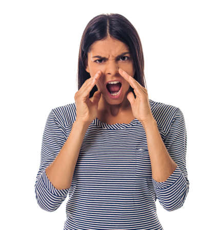 choleric: Beautiful young angry girl in casual clothes is screaming at camera, isolated on white