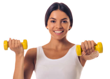white singlet: Beautiful young sportswoman in white singlet is holding dumbbells, looking at camera and smiling, isolated on white. Hand in focus