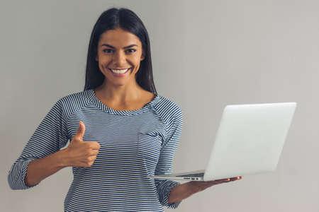Hermosa joven en ropa casual es la celebración de un ordenador portátil, que muestra el signo OK, mirando a la cámara y sonriendo, sobre fondo gris