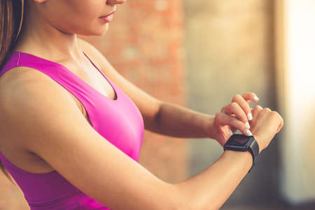 Cropped image of beautiful sports girl is switching on her fitbit before training while standing in fitness hall