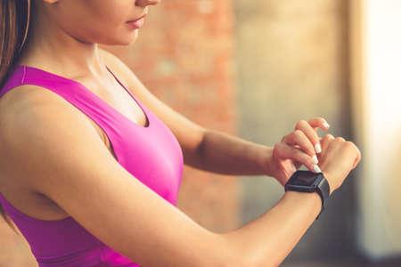 Freigegebenes Bild des schönen Sportmädchens schaltet ihr Fitbit vor dem Training ein, während er im Fitnessraum steht Standard-Bild