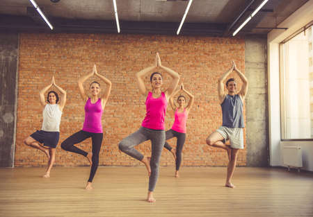 tree position: Beautiful sports people are standing in tree position and smiling while doing yoga in modern fitness hall