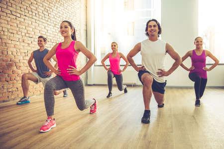 Mooie sportenmensen doen oefeningen en glimlachen terwijl het uitwerken in moderne fitnesszaal