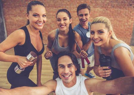 Mooie sport team houden sportartikelen, camera kijken en glimlachen terwijl het doen selfie in de fitness zaal Stockfoto