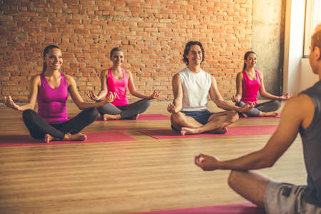 Beautiful sports people are sitting in lotus position and smiling while doing yoga with a trainer in modern fitness hall Stock Photo