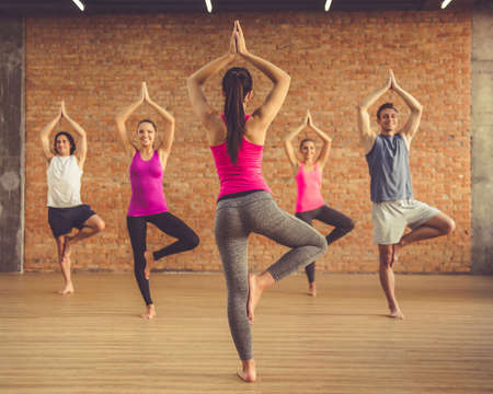 tree position: Beautiful sports people are standing in tree position and smiling while doing yoga with trainer in modern fitness hall