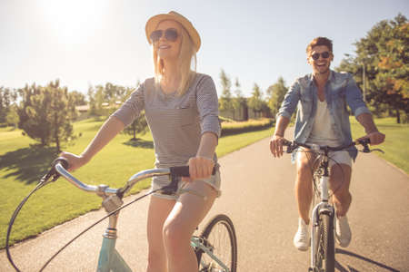 stylish couple: Beautiful stylish couple is smiling while cycling in the park Stock Photo