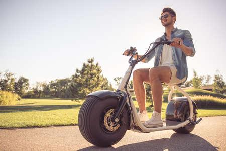 Bel homme élégant est souriant alors qu'il circulait sur le scooter électrique dans le parc