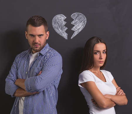 broken back: Beautiful young couple is looking at camera while standing back to back with folded arms against blackboard with drawn broken heart overhead