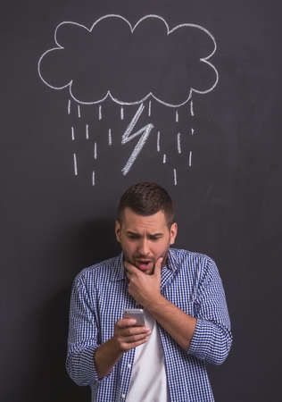 affraid: Handsome young man is using smartphone and showing fear, standing against blackboard with drawn rain cloud with lightning overhead Stock Photo