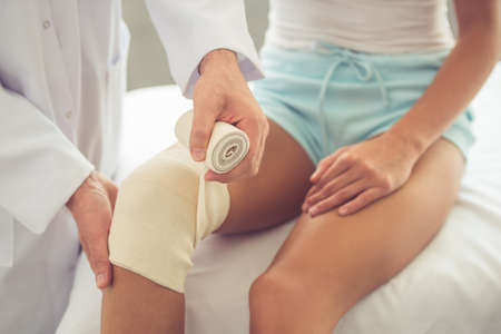 kneecap: Cropped image of handsome doctor bandaging womans injured knee while working in his office