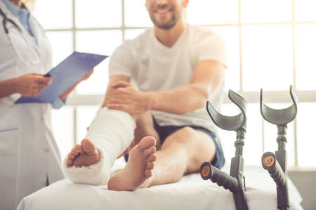 Cropped image of beautiful female medical doctor listening to handsome patient with broken leg and making notes while working in her office Stock Photo