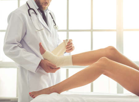 Cropped image of handsome doctor bandaging womans injured leg while working in his office