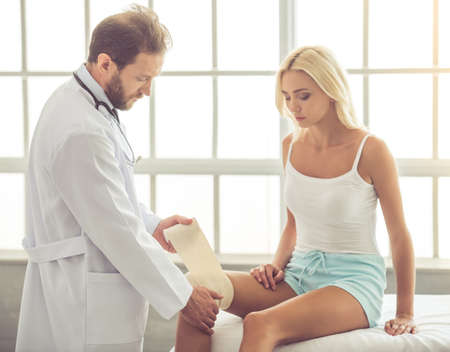 kneecap: Handsome doctor bandaging beautiful womans injured knee while working in his office