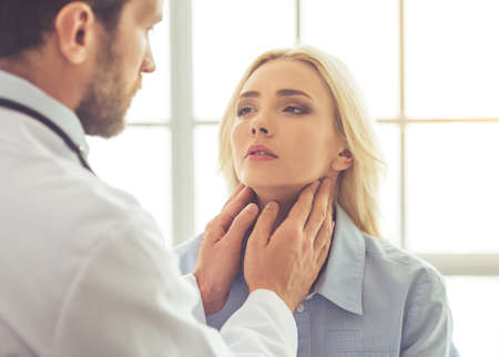 Handsome doctor is examining female patients injured neck while working in his office Stock Photo