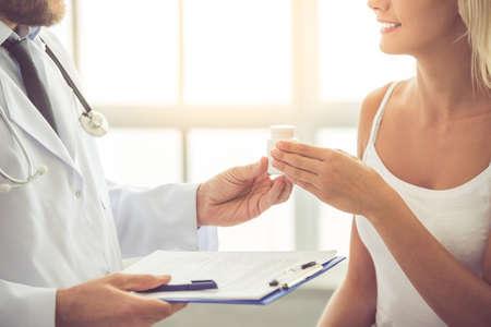 luxacion: Imagen recortada de médico guapo hablando con paciente femenino con rodilla lesionada y dando su medicina mientras trabajaba en su oficina