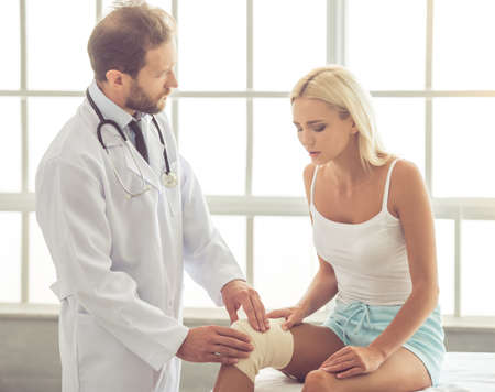 dislocation: Handsome doctor bandaging beautiful womans injured knee while working in his office