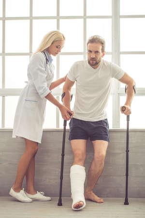 Mooie vrouwelijke arts helpt haar knappe patiënt met een gebroken been