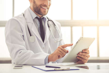 Cropped image of handsome medical doctor in white coat using a digital tablet and smiling while working in his office Stock fotó