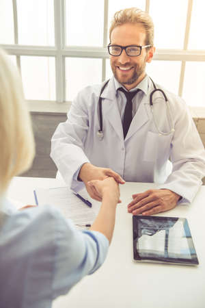 Handsome medical doctor in eyeglasses is shaking hands with female patient and smiling while working in his office