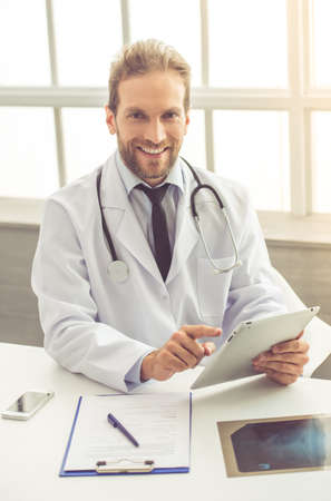 Handsome medical doctor in white coat is using a digital tablet, looking at camera and smiling while working in his office