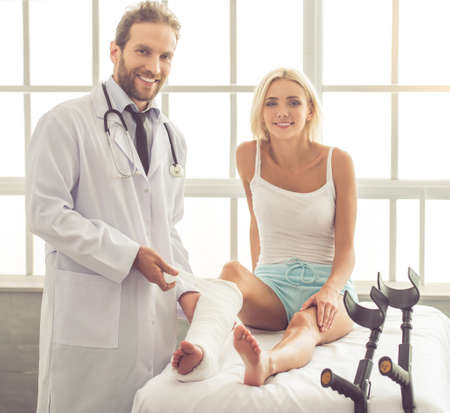 Handsome medical doctor is bandaging woman's broken leg while working in his office. Both are looking at camera and smiling