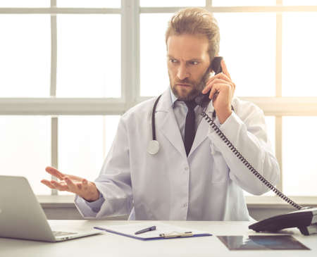 embarrassment: Handsome medical doctor in white coat is showing embarrassment while talking on the phone in his office Stock Photo