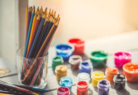 paint tool: Colored pencils and paint on table. Perfect stuff for the artist
