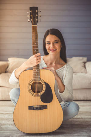 Attractive young girl is holding a guitar, looking at camera and smiling while sitting on the floor at home