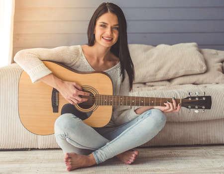 魅力的な若い女の子のギター、カメラを見て、家の床に座って笑顔 写真素材