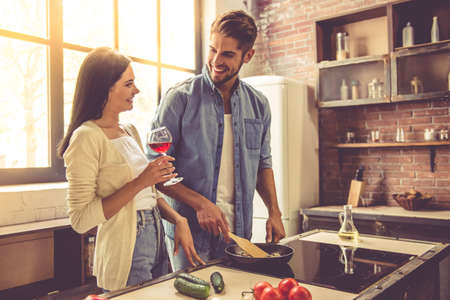 Beautiful young couple is talking and smiling while cooking in kitchen at home. Woman is drinking wine while her man is frying food