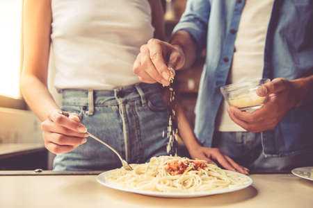 young add: Cropped image of beautiful young couple eating spaghetti in kitchen at home. Man is adding grated cheese