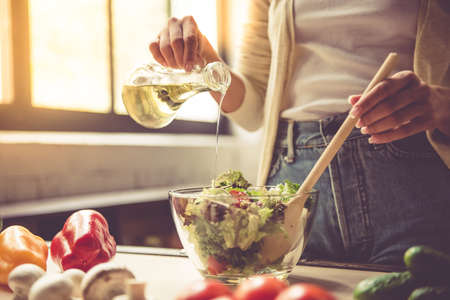 Cropped image of beautiful young girl mixing salad while cooking in kitchen at home