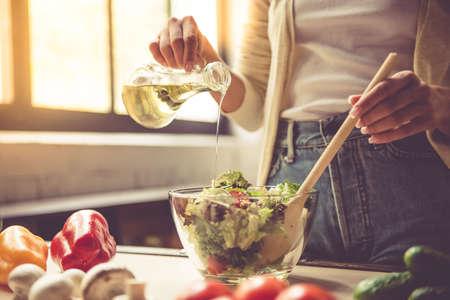 집에서 부엌에서 요리하는 동안 샐러드를 혼합 아름 다운 젊은 여자의 잘린 된 이미지
