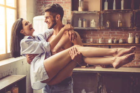 Sexy junger Mann mit nacktem Oberkörper hält seine schöne Freundin in den Armen, während in der Küche zu Hause stehen. Beide sahen einander an und lächeln
