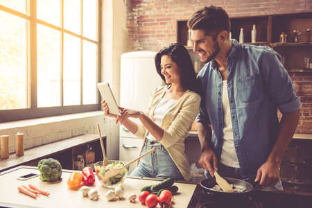 Beautiful young couple is using a digital tablet and smiling while cooking in kitchen at home Stock Photo